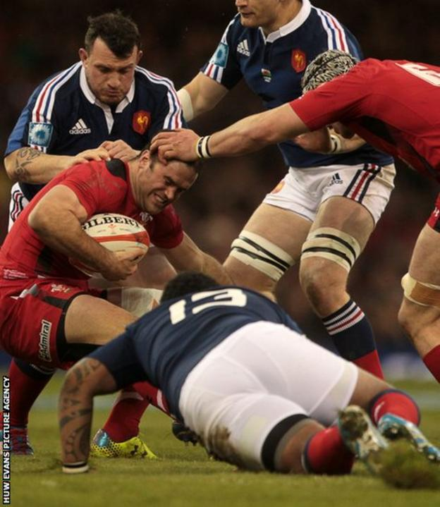 Wales and Racing Metro centre Jamie Roberts is tackled by French pair Thomas Domingo and Mathieu Bastareaud.