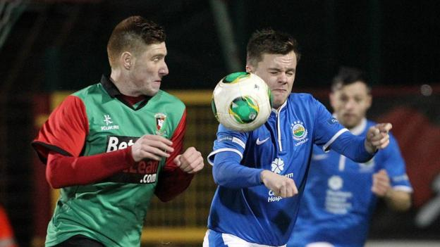Glentoran debutant Kym Nelson and Linfield's Niall Quinn battle for possession at the Oval