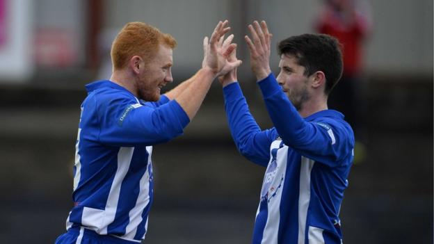 Joe McNeill congratulates Coleraine goal-scorer Eoin Bradley after the Derry GAA star opened the scoring against Portadown