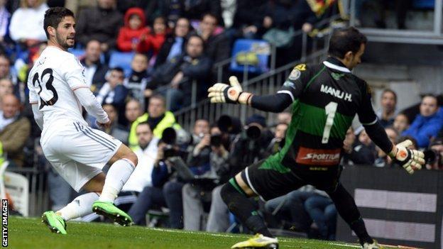 Real Madrid's midfielder Isco (left) scores past Elche's goalkeeper Manu Herrera