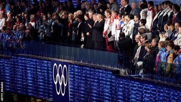 Russia's President Vladimir Putin waves next to International Olympic Committee (IOC) President Thomas Bach