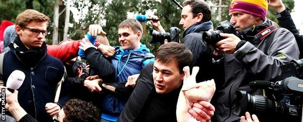 A member of a pro-Kremlin youth organisation throws a chicken during a press conference held by protest group Pussy Riot