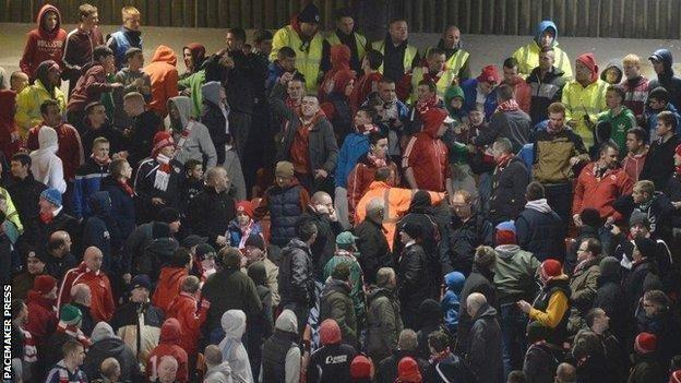 Stewards go into the Cliftonville end during the game against Linfield