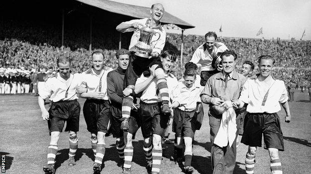 Charlton Athletic captain Don Welsh, holding the FA Cup, and winning goalscorer Chris Duffy (r, background) are chaired by their teammates during the lap of honour after the 1947 FA Cup final
