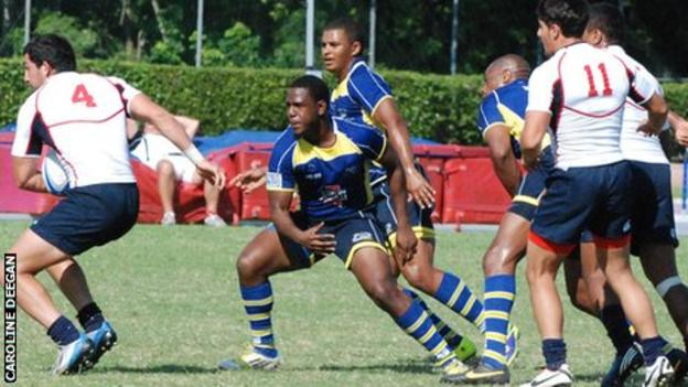 Barbados rugby sevens, in blue, in action against the USA.