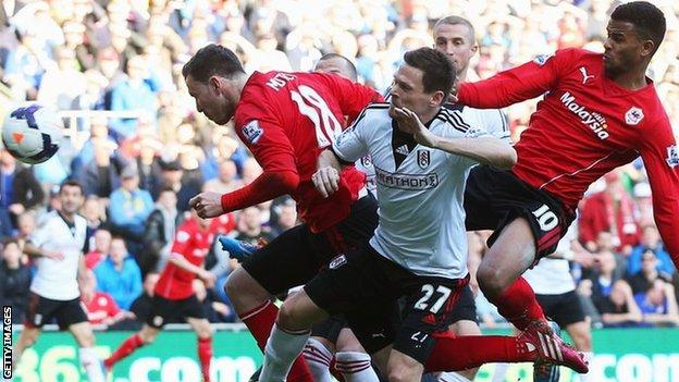 Sascha Riether of Fulham (27) scores an own goal for Cardiff City's third as he is challenged by Jordon Mutch (18) and Fraizer Campbell