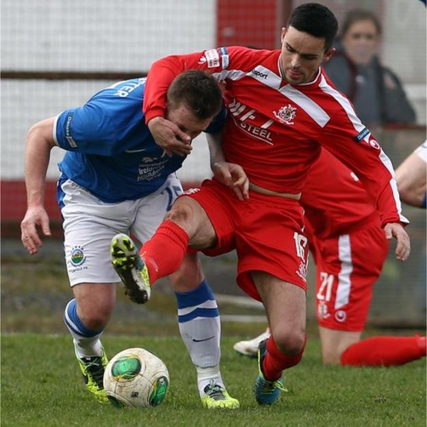 Linfield's Mark McAllister attempts to retain possession under pressure from Portadown opponent Neil McCafferty
