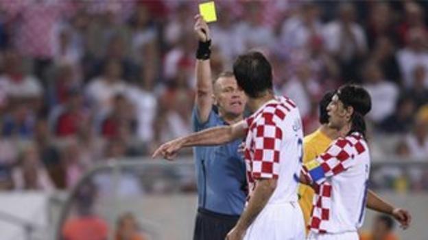 Graham Poll gives Croatia's Josip Simunic a yellow card