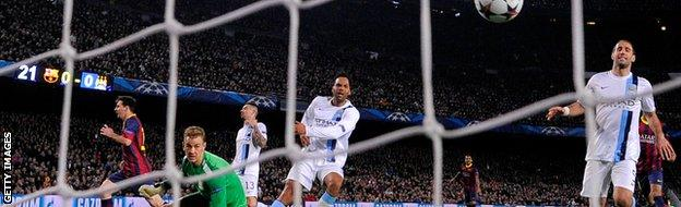 Lionel Messi (L) of Barcelona turns away to celebrate after scoring his team's opening goal during the UEFA Champions League Round of 16, second leg.