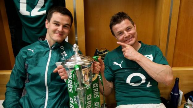 Jonathan Sexton and Brian O'Driscoll celebrate with the Six Nations trophy in the Irish dressing room after the game