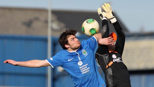 Philip Lowry challenges Gareth Buchanan during the Premiership game at Windsor Park