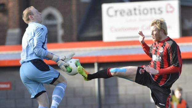 Ballymena goalkeeper Aaron Shanahan collects the ball as former United striker Andy Smith closes in