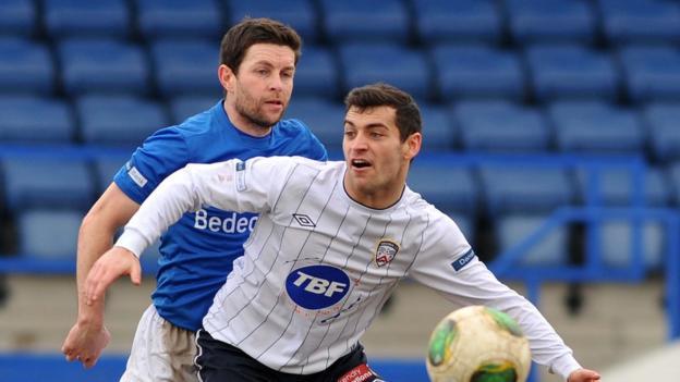 Glenavon defender Eddie McCallion prepares to challenge Coleraine forward David McDaid at Mourneview Park