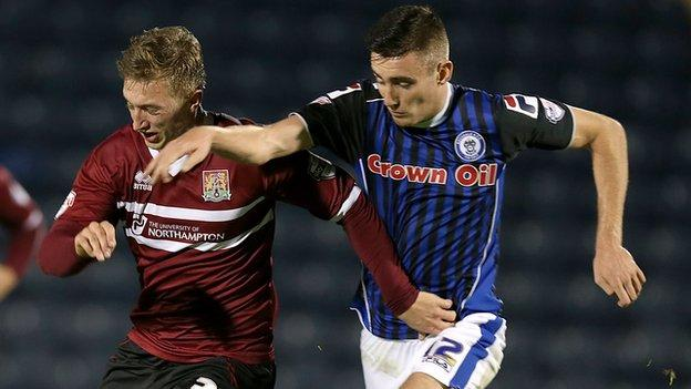 Northampton's Luke Norris is challenged by Rochdale scorer Matthew Lund, who was sent off for celebrating his goal.