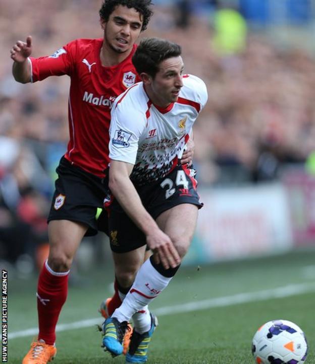 Liverpool's Welsh midfielder Joe Allen gets the better of Cardiff City full-back Fabio