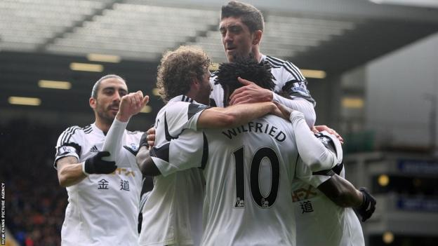 Striker Wilfried Bony is mobbed by his team-mates after cancelling out Leighton Baines's penalty to bring Swansea level against Everton.