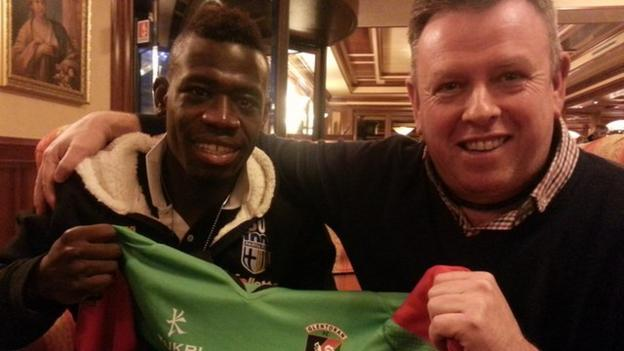 Afriyie Acquah (left) holds a Glentoran shirt with Sam Robinson, whose family he lived with in Belfast
