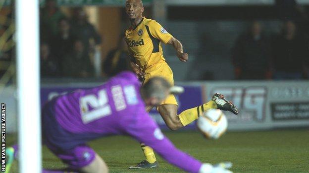 Bury goalkeeper Brian Jensen saves Newport striker Chris Zebroski's shot