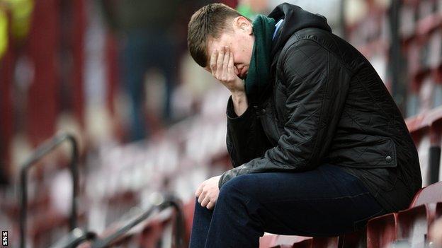 A Hibs fan looks dejected
