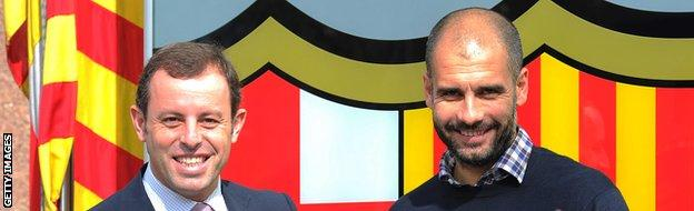 Barcelona's coach Josep Guardiola (R) shakes hands with Barcelona's Sandro Rosell (L) on February 23, 2011 at Camp Nou stadium in Barcelona after signing his one-year contract extension.