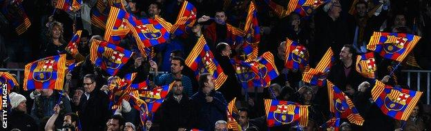 Barcelona fans wave their flags during the UEFA Champions League Quarter Final first leg match between FC Barcelona and Club Atletico de Madrid at Camp Nou on April 1, 2014.