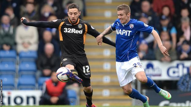 In League Two, Newport County's Robbie Willmott tries to shield the ball away from Chesterfield midfielder Daniel Kearns.