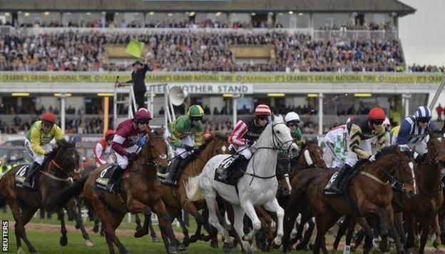 Horses and riders get under way as the starter (background) waves his flag for a false start