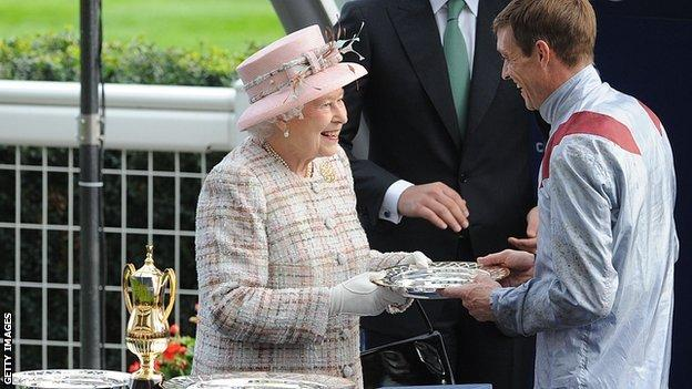 The Queen presents jockey Richard Hughes with his prize on Champions Day 2013