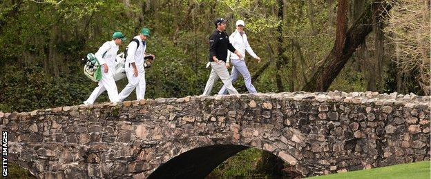 Rory McIlroy of Northern Ireland (right) and Patrick Reed of the US cross the Nelson Bridge on the 13th at Augusta during practice this week