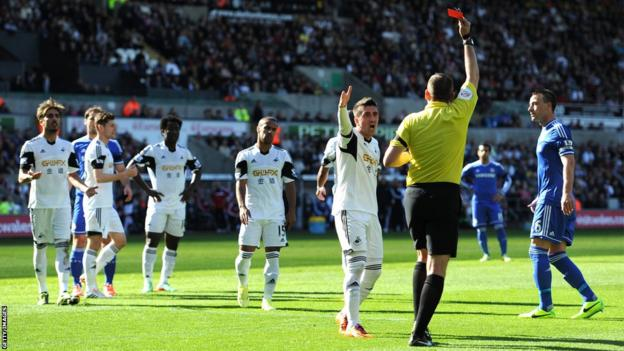 Swansea's Pablo Hernandez of Swansea remonstrates with Referee Phil Dowd as he shows the red card to Chico Flores (left) after 16 minutes