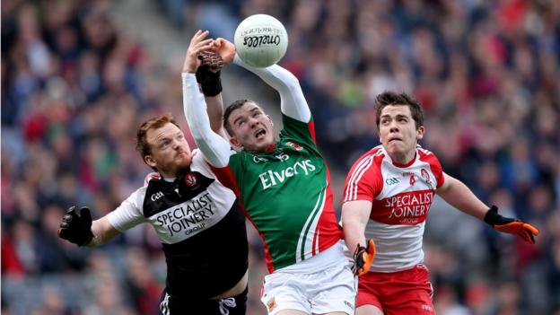 Thomas Mallon and Dermot McBride challenge for the ball with Mayo's Mickey Sweeney