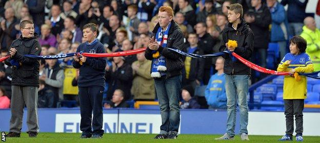 Everton supporters join their scarves with Liverpool FC scarves to mark the 25th anniversary of the Hillsborough disaster before the game.