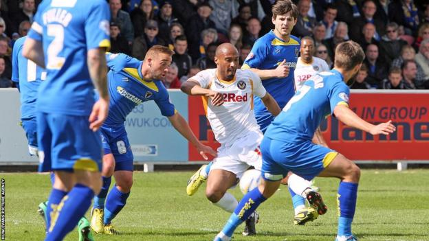 Chris Zebroski scores Newport County's opening goal in their Good Friday game at AFC Wimbledon in League Two.