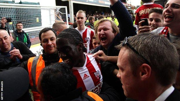 Clayton Donaldson is mobbed by Brentford fans after the Bees won promotion to the Championship
