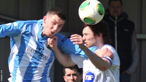 Warrenpoint striker Daniel Hughes in an aerial duel with Coleraine's Howard Beverland