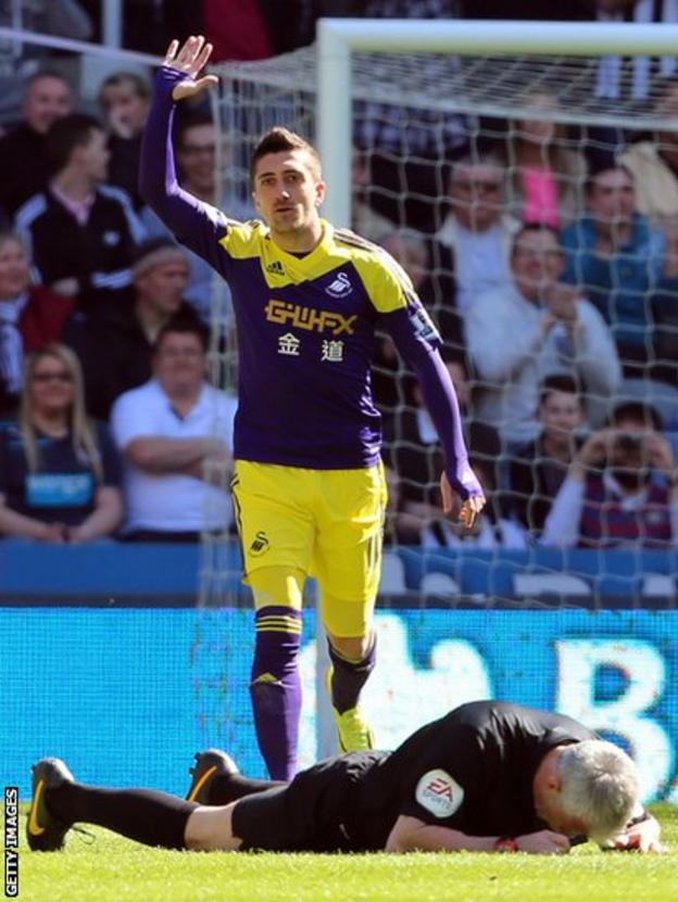 Swansea City's Pablo Hernandez asks for help for referee Chris Foy after the official was hit in the face by the ball