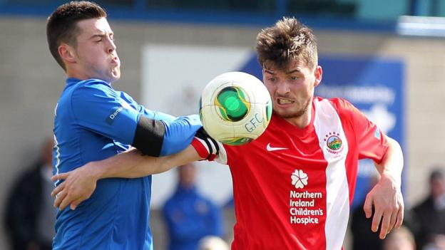 Sammy McIlveen of Glenavon battles for possession with Philip Lowry during the Irish Premiership game at Mourneview Park which Linfield won 5-2