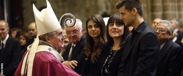 "Archbishop Lluis Martinez Sistach (L) speaks to former Barcelona coach Tito Vilanova""s wife Montse (2nd R), son Adria"