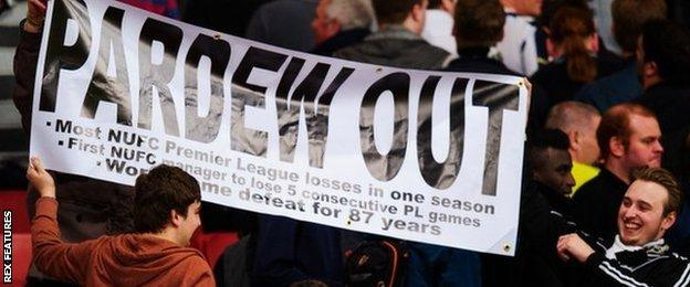 Newcastle fans hold up a 'Pardew Out' banner at the Emirates Stadium