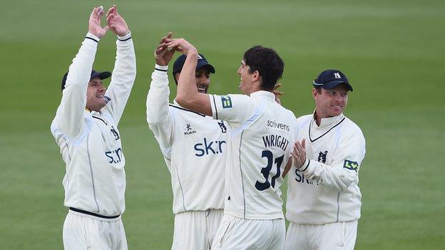 Warwickshire players celebrate Chris Wright's one of match hau