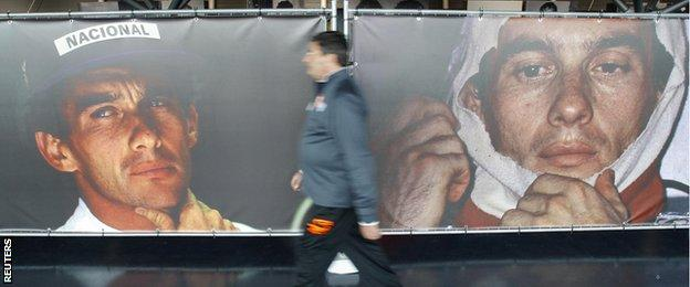 A man walks past pictures of Senna at an exhibition at the Imola race track