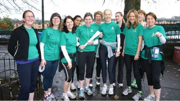 Louise Love (holding a baton) with her running group