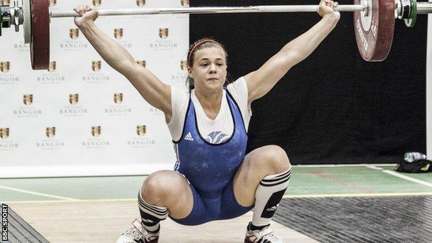 Rebekah Tiler hoists weights above her head with her knees bent