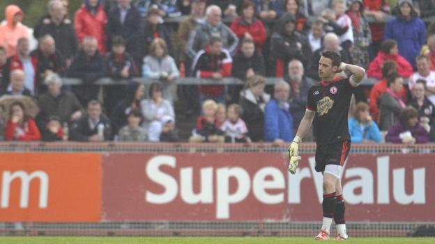 Tyrone keeper Niall Morgan makes the long walk off the field after he was back-carded by referee David Coldrick