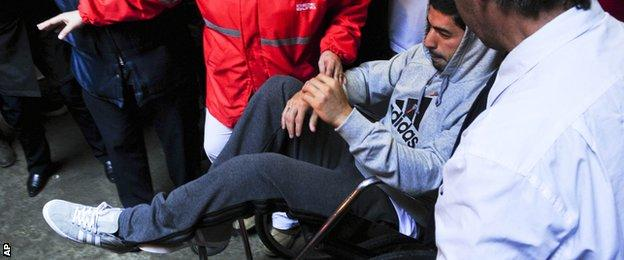 Luis Suarez in a wheelchair after knee surgery