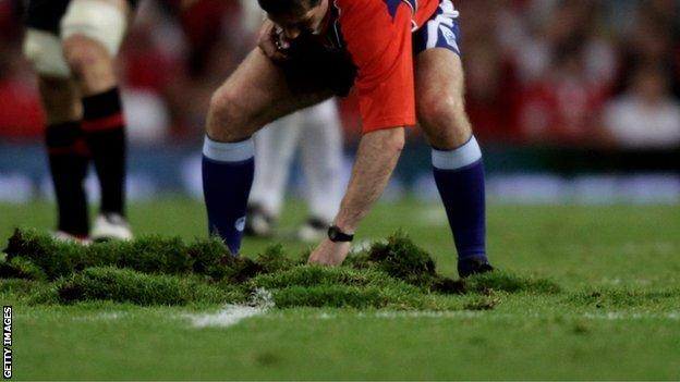 Referee Alain Rolland tries to repair part of Millennium Stadium pitch in 2009