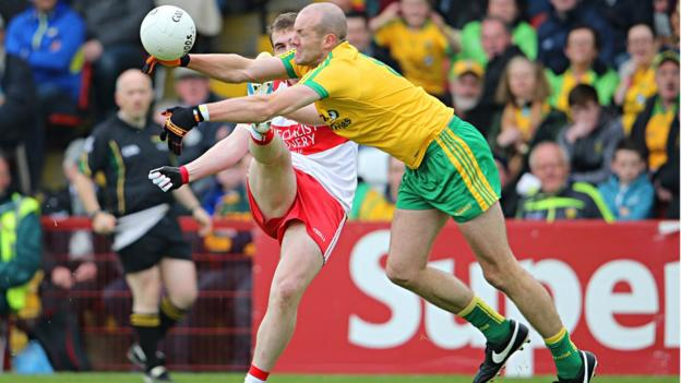 Ryan Bell of Derry gets the ball away as Donegal's Neil Gallagher attempts to block