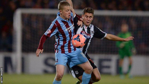 Terry Hawkridge (L) of Scunthorpe United challenges Scott Neilson of Grimsby Town during their FA Cup First Round Replay at Glanford Park