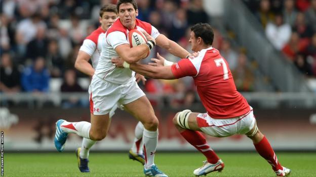James Hook, playing at fly-half for the Possibles team in the Wales trial match, is tackled by Probables flanker Aaron Shingler.