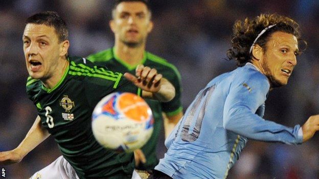 Northern Ireland's Chris Baird competes against Diego Forlan of Uruguay